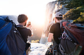 Rear view of two men taking pictures of rocks and a sunset with a mobile phone.
