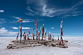 An outcrop of rocks on the salt flats with flags of many countries below a blue sky.