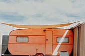 Exterior view of vintage orange camper van with sun-sail on Fuerteventura.