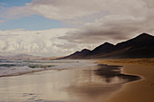 View along a sandy beach on Fuerteventura on a cloudy day.