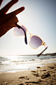 Close up of person on sandy beach, holding sunglasses towards the sun.