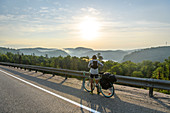 Cyclist stopping on road with scenic view, Ontario, Canada