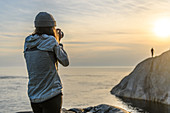 Photographer at coast, photographing friend in distance, Ontario, Canada