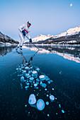 Ice hockey player man skating on Lake Sils covered in  ice bubbles at dusk, Engadine, Graubunden canton, Switzerland, Europe