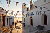 Sunset in Plaka, the main town on Milos island, with Greek Orthodox feast decoration on the church square with pebble mosaic, Plaka, Milos, Cyclades, Greek Islands, Greece, Europe