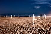 Beach volleyball nets on sand on beach.