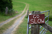 Go slow sign on wooden countryside gate.