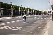WOMAN WITH A MASK CROSSING THE NEARLY DESERTED RUE DE RIVOLI DURING THE COVID-19 PANDEMIC LOCKDOWN, PARIS, ILE DE FRANCE