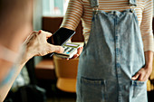 Woman wearing face mask behind cafe counter holding contactless payment device while customer uses mobile phone to pay bill