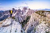 Man on top of rocks photographing Cadini di Misurina at sunrise, Dolomites, Belluno province, Veneto, Italy, Europe