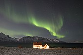 The typical house illuminated by lights and Northern Lights, Lyngen Alps, Tromso, Norway, Europe