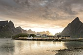 Midnight sun on the fisherman village frames by rocky peaks and sea Sakrisoya, Nordland county, Lofoten Islands,Northern Norway, Europe