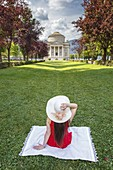 A tourist sitting on Como gardens looks a Volta Temple monument (Tempio Voltiano), Como city, Lombardy, Italy, Europe (MR)