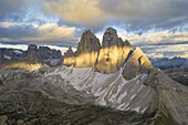 the majestic Tre Cime di Lavaredo, shot by a photographer with a helicopter during a sunset with warm light, Dolomiti, Unesco World Heritage Site, belluno province, Veneto district, Italy, Europe
