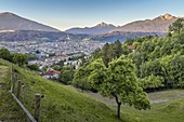 The city of Innsbruck at dawn with Patscherkofel and Serles in the background as seen from the road that leads to Hungerburg, Tyrol, Austria, Europe