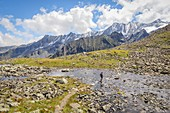 A man hiking through Rinnenkarbach with the Sommerwand and the Stubai Alps in the background, Neustift, Innsbruck Land, Tyrol, Austria, Europe
