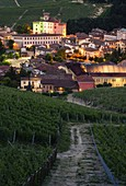 Barolo Castle through the vineyards coloured with the italian flag at dusk, Barolo, Piedmont, Italy