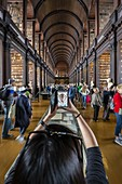 View of a tourist taking pictures with a smartphone of the interior of the Trinity College library, Dublin, Ireland, Europe.