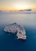 Aerial view of Isola Foradada island in front of the rocky promontory of Capo Caccia at sunset, Alghero,  Sassari district, Sardinia, Italy.