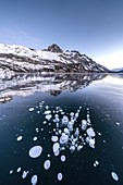 Ice bubbles trapped in the frozen Lake Sils, canton of Graubunden, Engadine, Switzerland
