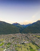 Cultivated fields around Morbegno and Orobie Alps at sunset, aerial view, Valtellina, Sondrio province, Lombardy, Italy