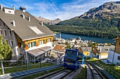 Funicular moving uphill crossing the alpine village of St. Moritz, Engadine, canton of Graubunden, Switzerland
