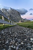 Footpath towards majestic Sassopiatto and hut at sunset, Alpe di Siusi/Seiser Alm, Dolomites, South Tyrol, Italy