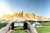 Personal perspective of tourist photographing the Odle with smartphone at sunset, Val di Funes, South Tyrol, Dolomites, Italy