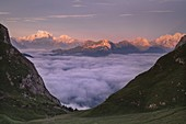The dense clouds cover the Val Fiorentina while from Mondeval the group of the Pale di San Martino with the Mulaz stand out illuminated by the colors of a summer dawn