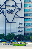 Building with image of Fidel Castro and classic car on Plaza de La Revolución in Havana, Cuba