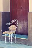 Old iron chair on sidewalk in Havana, Cuba