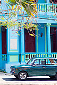 Classics car in front of a blue building in Pinar del Rio, Cuba