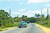 Classic green car driving through the Viñales Valley in Cuba