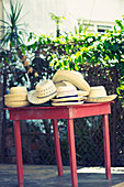 Braided straw hats on a red table in Viñales, Cuba