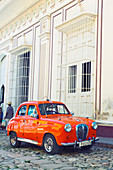 Classic red car in front of a white building in Trinidad, Cuba