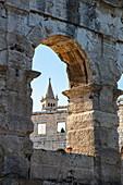 Church tower seen through archway of Roman amphitheater, Pula Arena, Pula, Istria, Croatia, Europe