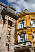 Contrast between columns of the old Roman arch of the Sergii and new building, Pula, Istria, Croatia, Europe