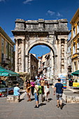 Pedestrians and the ancient Roman arch of the Sergii in the center of the old town, Pula, Istria, Croatia, Europe