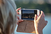 Woman photographs old town with smartphone as seen from  ship, Rab, Primorje-Gorski Kotar, Croatia, Europe