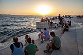 People gather along the seaside promenade to listen to the sea organ at sunset, Zadar, Zadar, Croatia, Europe