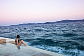 Young woman in bikini sitting on steps of the sea promenade at sunset, Zadar, Zadar, Croatia, Europe