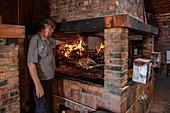 Man grills meat in the Macola restaurant, Korenika, Lika-Senj, Croatia, Europe
