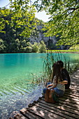 Couple sits on wooden plank path and admires clear water in a pool, Plitvice Lakes National Park, Lika-Senj, Croatia, Europe
