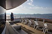 Couple and deck chairs on board the cruise ship at sunrise, Kornati Islands National Park, Šibenik-Knin, Croatia, Europe