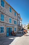 Couple walks arm in arm through the old town, Primosten, Šibenik-Knin, Croatia, Europe