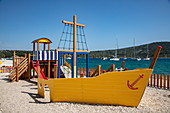 Playground for children on the beach with yellow boat, Primosten, Šibenik-Knin, Croatia, Europe