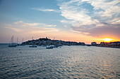 Sailboats moored in the harbor with old town in the distance at sunset, Primosten, Šibenik-Knin, Croatia, Europe