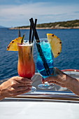 Detail of two colorful cocktails in the hands of passengers on board the cruise ship, Vis, Vis, Split-Dalmatia, Croatia, Europe