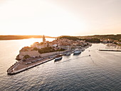 Aerial view of the cruise ship and other boats that have moored at the old town at sunset, Rab, Primorje-Gorski Kotar, Croatia, Europe