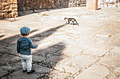 Child watches the cat in Marbella, Spain